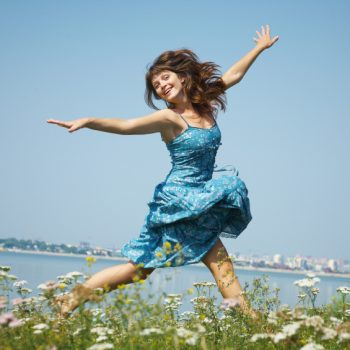 Young woman jumping on the meadow blue sky against